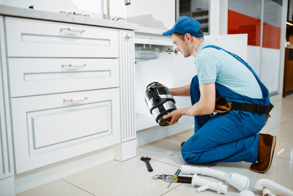 Male plumber in uniform installing disposer