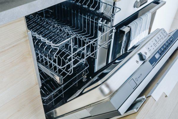 Open empty dishwasher machine close-up in modern kitchen.